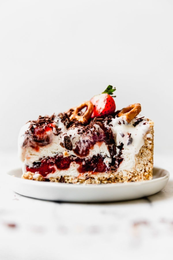 A sideview of a thick slice of Strawberry Pretzel Ice Cream Pie on a small white plate.