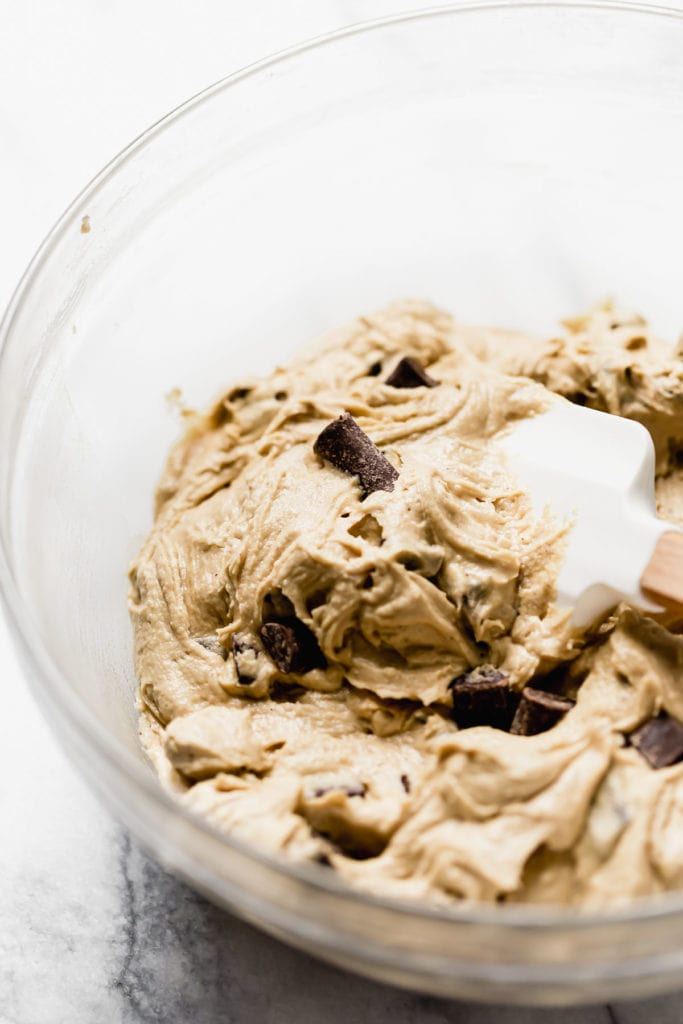 A glass bowl with chocolate chunk cookie dough and a spatula.