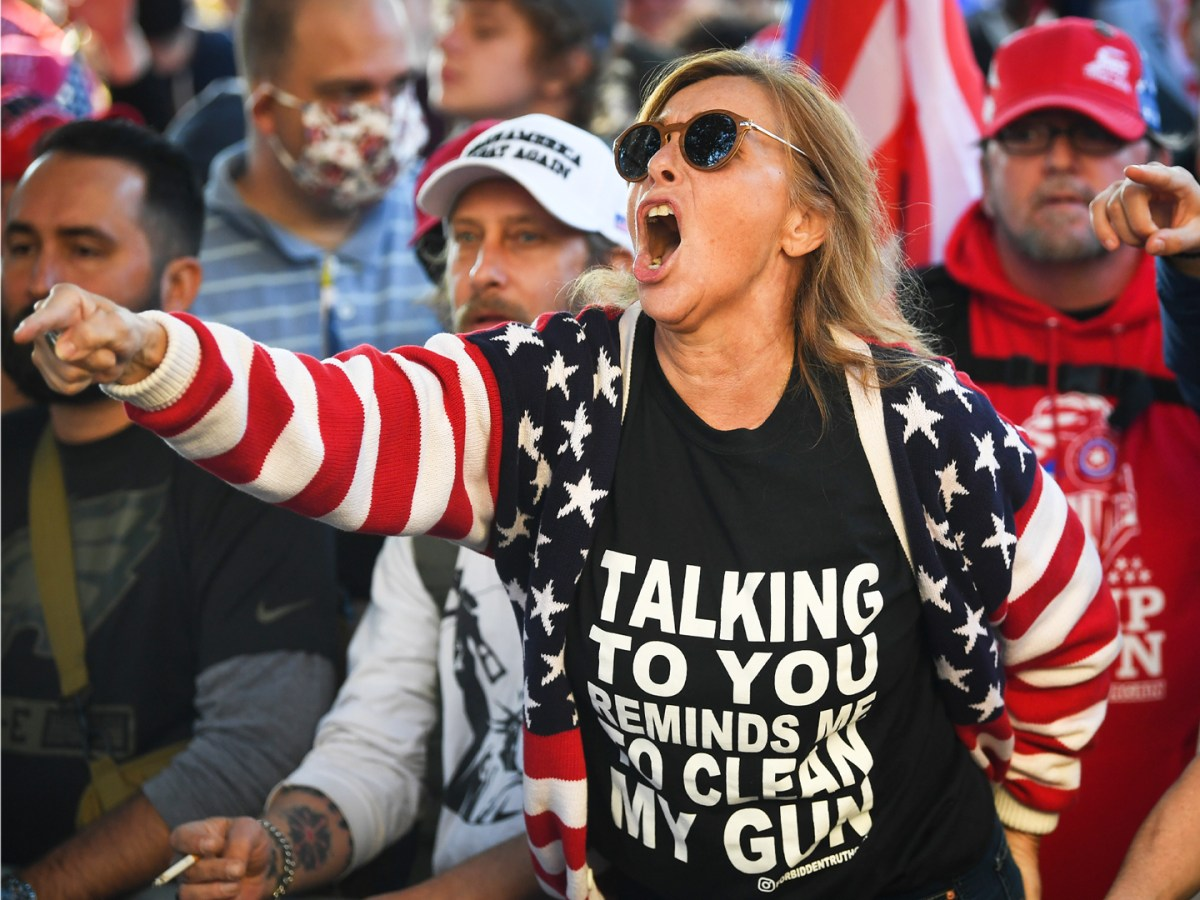 A Trump supporter yells at counter-protesters outside of the U.S. Supreme Court during the Million MAGA March