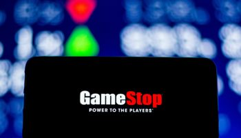 A GameStop logo is seen displayed on a smartphone with the capital stock numbers in the background