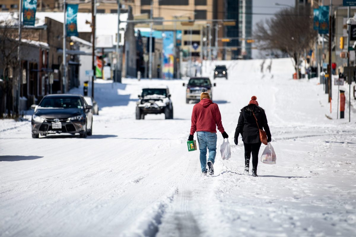 People carry groceries through the snow in Austin, Texas.