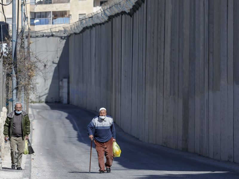 Palestinian men walk by Israel's controversial barrier separating the West Bank city of Abu Dis (background) and East Jerusalem