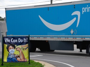 An Amazon Prime delivery truck passes a RWDSU Vote Yes sign