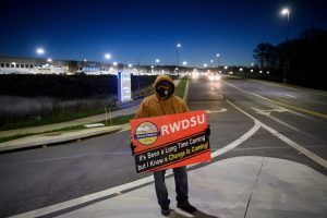 A union supporter stands before sunrise outside the Amazon.com, Inc. BHM1 fulfillment center on March 29, 2021 in Bessemer, Alabama