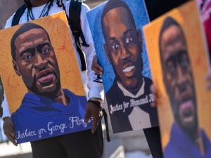 Community activists hold pictures of George Floyd and Ahmaud Arbery