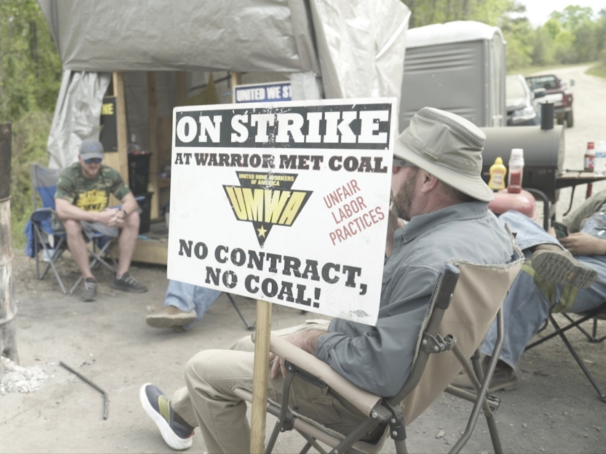 Striking coal miners sit on a picket line