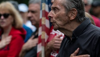 A man sings the national anthem at a rally against critical race theory being taught in schools