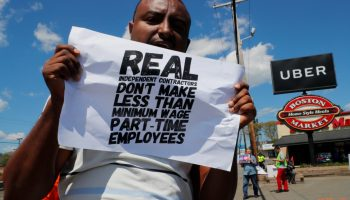 Uber and Lyft drivers protest during a day-long strike outside Uber's office in Saugus