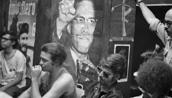 Members of the Young Patriots Organization sit under a poster of Malcolm X