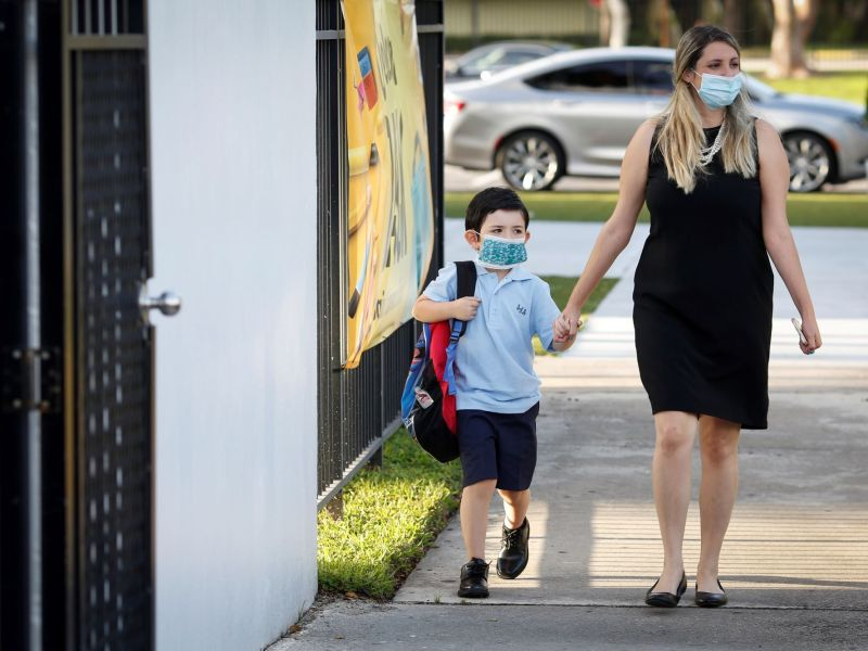 Wearing protective masks, a teacher walks to class with a student