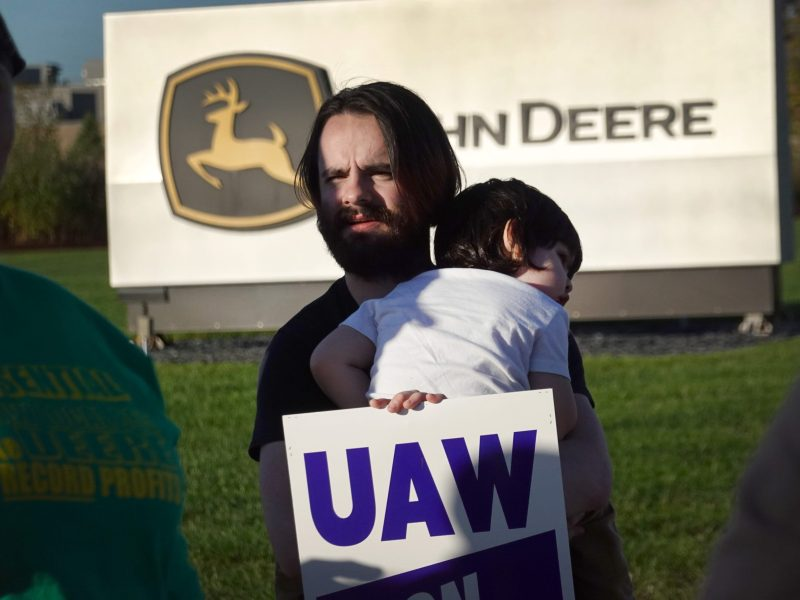 Robert Ferreira pickets with his son Rafael outside of John Deere Harvester Works facility