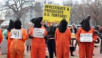 Protesters, wearing orange prisoner jumpsuits symbolizing Guantanamo Bay detainees