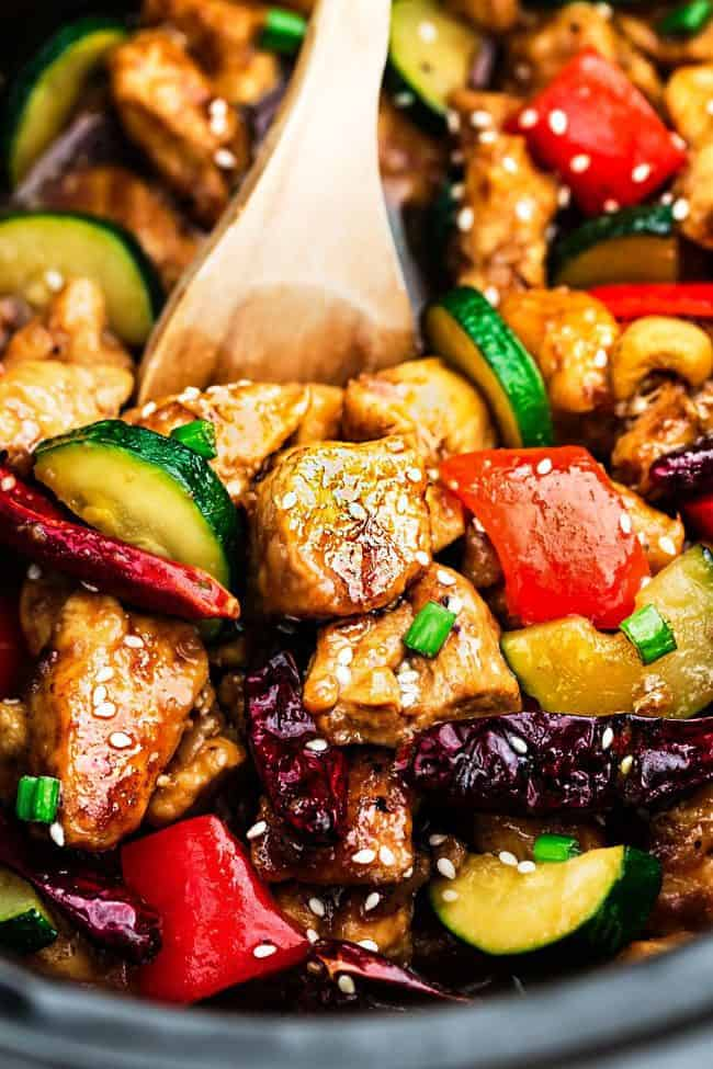 Skinny Slow Cooker Kung Pao Chicken unclose photo with a wooden spoon.