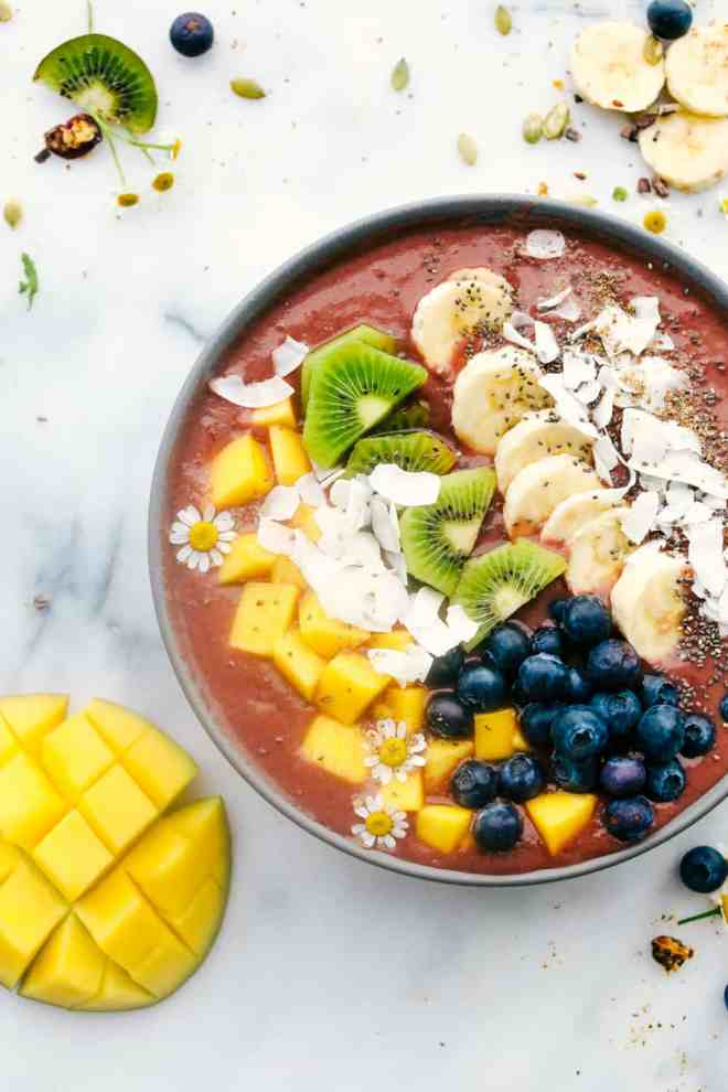 Tropical Mango acai bowl with fruit toppings and a fruit ingredients on the side.