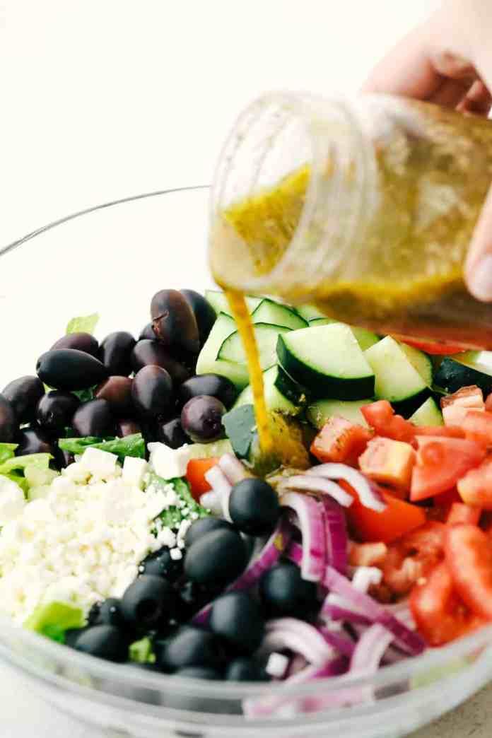 Pouring dressing on Greek salad ingredients.