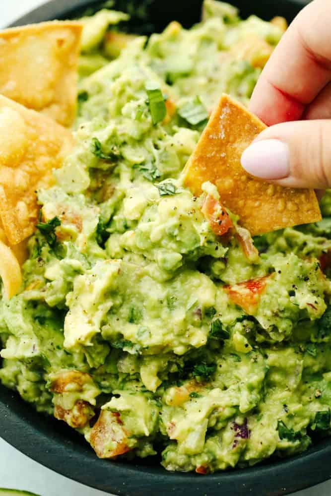 Dipping a chip into guacamole.