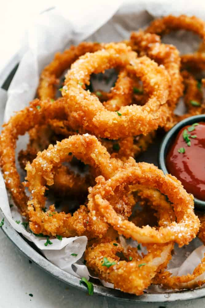 Finished onion rings on a plate with dipping sauce.
