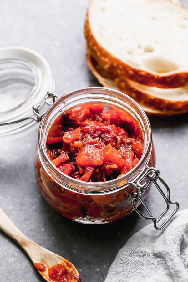 Tomato jam in a clear jar with a wooden spoon and three slices of bread surrounding the jar.