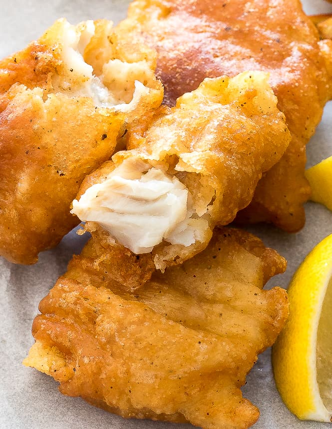 Fried fish on parchment paper with a slice of lemon next to it.