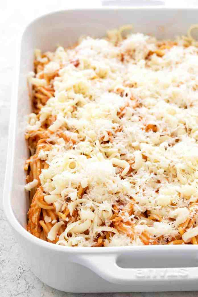 Lots of shredded cheese in a casserole dish with pasta