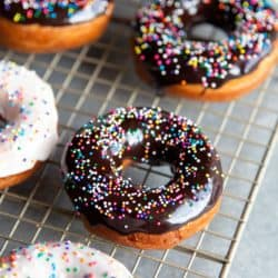 Glazed donuts with sprinkles on a wire rack