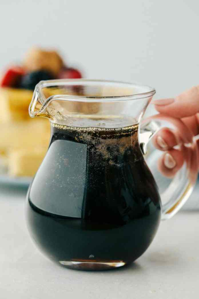 Homemade maple syrup in a pourable glass pitcher.