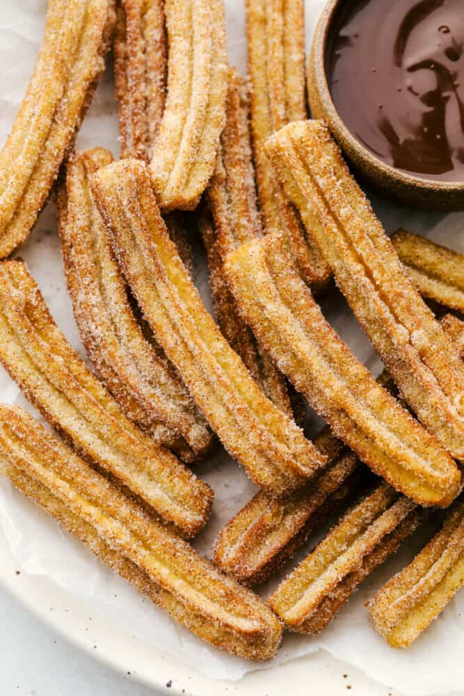 A pile of fried churros with a side of chocolate dipping sauce.