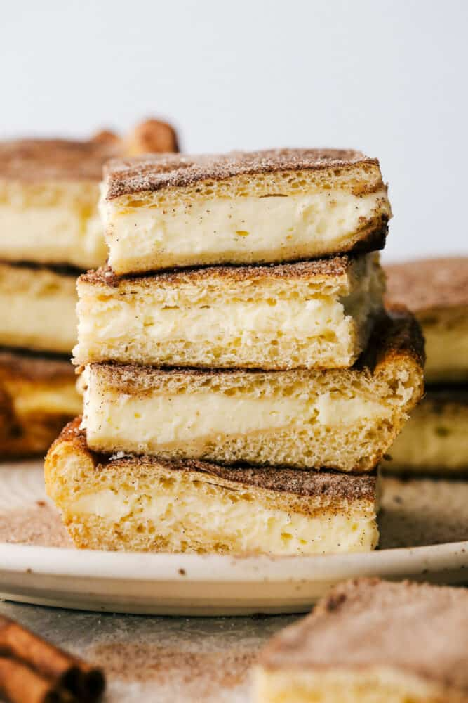 Churro Cheesecakes bars stacked on top of eachother.