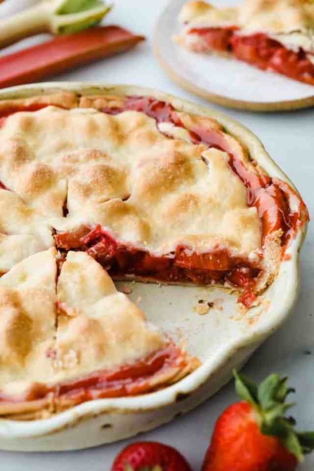Strawberry rhubarb pie with piece taken out of it