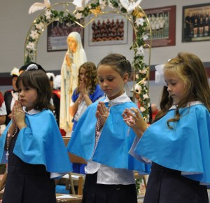 Maddie Hulsewede, Cecilia Casabella and Holland Hulsewede, from left to right, stood in their place as rosary ÒbeadsÓ during the 63rd annual ÒLiving Rosary ProcessionÓ held Oct. 5 at Assumption High School. School age children form the shape of the rosary during the presentation. Each child sits down when the prayer he or she represents is prayed. (Record Photo by Jessica Able, 2014)