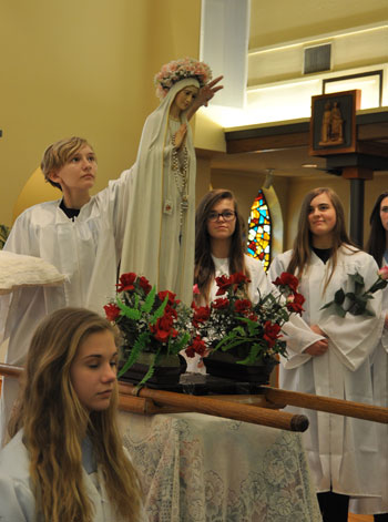 An eighth-grade student at St. Bernard School crowned a statue of Mary May 7 at St. Bernard Church.