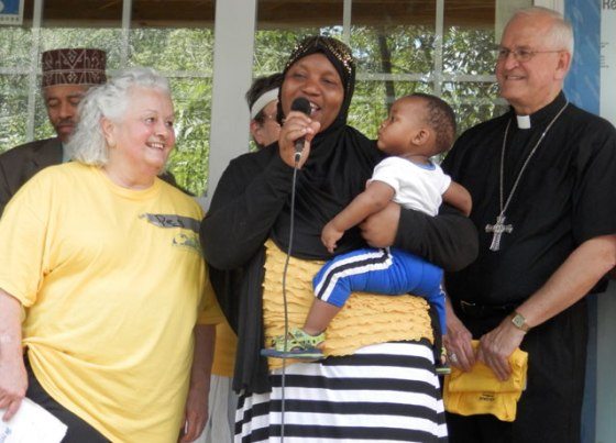 """Peg Schervish, left, and Archbishop Joseph E. Kurtz looked on as Bisharo Hussein, center, thanked Habitat for Humanity volunteers during a ceremony, May 30, during a blessing of the """"Wake Up the World"""" house. The house on Hazelwood Court, which is sponsored by religious communities, will be ready for her family to move into in a few months. (Record Photos by Ruby Thomas)"""