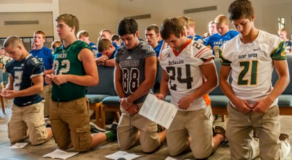 Athletes, from left, Aaron Flanagan, Noah Hoffman, Ryan Anderson, Taylor Stemmle and Patrick Ritter knelt in prayer at St. Patrick Church July 31, 2015. More than 500 athletes and coaches from Catholic high schools gathered at St. Patrick in Eastwood to pray the rosary in preparation for the fall sports season. The Rosary Rally, sponsored by SportsLeader, drew male athletes from Bethlehem, DeSales, Holy Cross, Trinity and St. Xavier high schools in the Archdiocese of Louisville and Our Lady of Providence Junior-Senior High School in Clarksville, Ind. (Photo Special to The Record by Father Patrick Delahanty