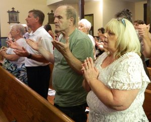 Parishioners of St. John Chrysostom Church in Eminence, Ky., prayed the Lord's Prayer during a Mass celebrated by Archbishop Joseph E. Kurtz Aug. 9 to consecrate a new altar. The new altar is part of a major renovation at the small parish. Record Photo by Marnie McAllister