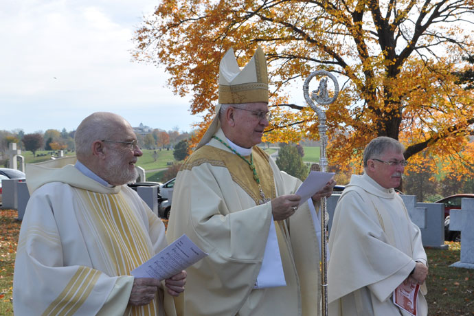 Deacon Robert Markert, Archbishop Joseph E. Kurtz and Father Jerry Bell sing the opening song at the All Souls' Day Mass Nov. 2 at Calvary Cemetery, 1600 Newburg Road.