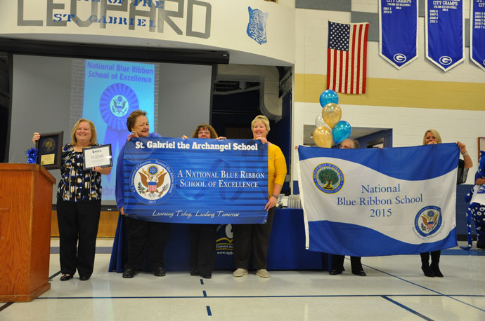 Pam Huelsman, principal of St. Gabriel School, and the blue ribbon award committee hold the award plaque, banner and flag they received at the official awards ceremony in Washington, D.C.