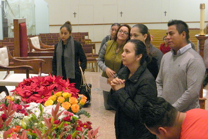 Parishioners, including Elisa Gutierrez in the foreground, prayed before an image of Our Lady of Guadalupe following Mass at St. Edward Church Dec. 12.