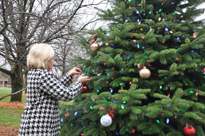 """Julie Borders, a family counselor at Catholic Cemeteries, placed an ornament on the """"tree of remembrance"""" at Calvary Cemetery, 1600 Newburg Road, Dec. 1. (Record Photos by Jessica Able)"""
