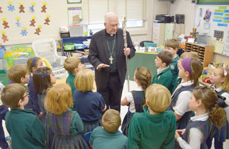 Archbishop Joseph E. Kurtz visited Holy Trinity School on March 2 and spoke to second-graders, above, about the Eucharist. He told students he would pray for them as they prepare for their first Eucharist on April 17. Presentation Academy Junior Abby Shipley, below, received ashes from Father Christopher Rhodes during an Ash Wednesday service at the school. (Photo Special to The Record)