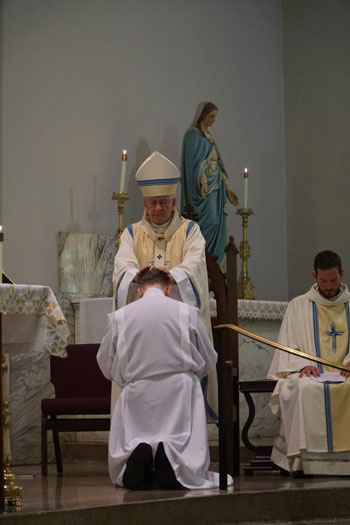 Archbishop Joseph E. Kurtz laid his hands on Deacon Michael Martin, above, during the ordination rite at Good Shepherd Church, Deacon Martin's home parish, on March 19.