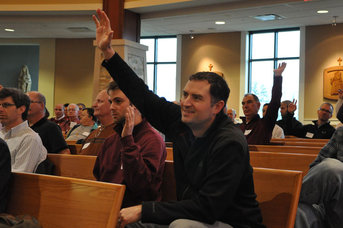 Amos Stinson, left, and Paul Burke, parishioners of St. Patrick Church, raised their hands in response to a question from Archbishop Joseph E. Kurtz at the Catholic Men's Conference March 5. (Record Photo by Jessica Able)