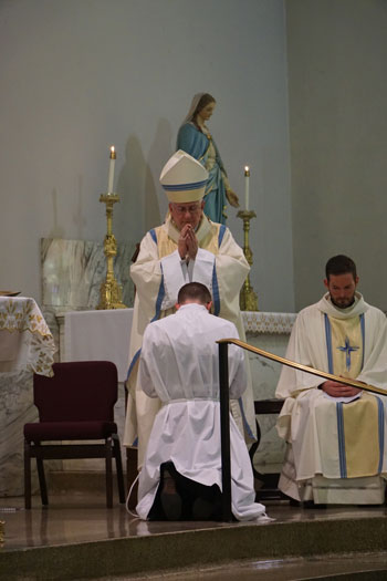 Archbishop Joseph E. Kurtz prayed over Deacon Sanders, below, during the diaconate ordination.