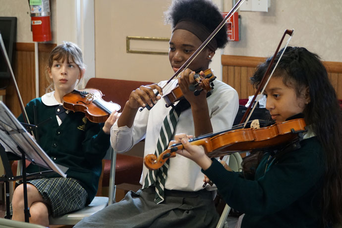 Cecilia Downs, left, Yohari Salama, center, and Jocelyn Olvera Lira practiced playing the violin during orchestra class at Corpus Christi Classical Academy in Simpsonville, Ky. Music is part of the school's curriculum and students enroll in the orchestra in the fifth grade. (Record Photo by Ruby Thomas)