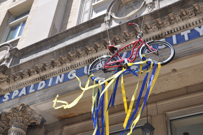 A red bike hangs in tribute to Muhammad Ali above the entrance to the former Columbia Auditorium, what is now the Spalding University Center. In 1954, a young Cassius Clay reported his stolen bicycle to Joe Martin, a police officer who also ran a boxing club in the building's basement. The gym where he trained is still in use by Spalding athletes today. (Record Photo by Jessica Able)