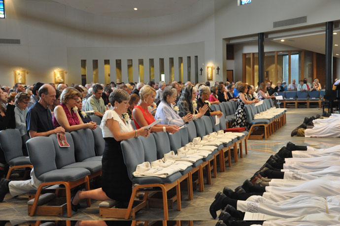 Wives of the men ordained to the permanent diaconate, above left, prayed during the Litany of Supplication at the Aug. 20 Ordination to the Order of Deacon. Above, Deacon Pat Wright, at right, the former director of the Diaconate Office, embraced the newly-ordained Deacon Stephen A. Age. Deacon Denny Nash, who became the new director of the Diaconate Office in May, looked on.  At left, Deacon James R. Turner, on the far right, assisted the newly-ordained Deacon Anthony T. Brown in vesting with the dalmatic and stole. Deacon Brown's wife, Naomi Marie Brown, far left, and Julie Fagan, the wife of Deacon Richard J. Fagan, assisted.  (Record Photos by Jessica Able
