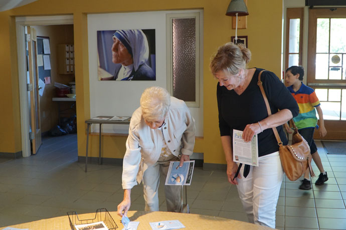 Yvonne Miller and Theresa Rennirt pick up St. Teresa of Kolkata prayer cards prior to Mass Sept. 4 at Blessed Teresa of Calcutta Church in Fairdale. Mother Teresa was canonized by Pope Francis on Sept. 4 during a Mass in St. Peter's Square.