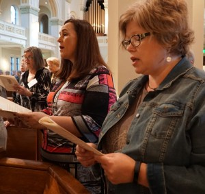 """Women from St. Patrick Church in Louisville, above foreground from left, Jonna O'Bryan and carrie Williamson, sang during the closing liturgy of the """"Women of the Church"""" conference Oct. 8."""