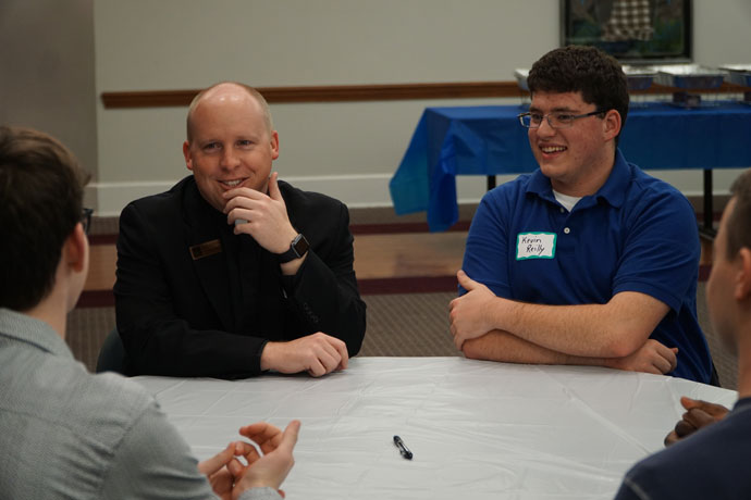 Father Shayne Duvall, associate vocation director, shared a laugh with young men, including Kevin Reilly, a graduate of St. Xavier High School who attends the University of Louisville's Speed School of Engineering, at a St. Andrew discernment dinner Oct. 28. (Record Photo by Jessica Able)
