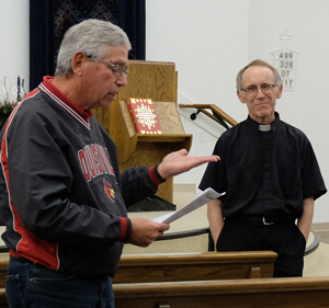 Father William P. Burks, at right, listened to Mike Kolb during a Nov. 29 gathering on the churchÕs justice ministry.  (Photos Special to The Record by Father Patrick Delahanty)