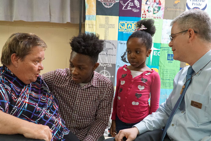 Dr. Carole Goodwin, left, spoke with Abraham Flomo, second from left,  and his sister Grace, parishioners of St. William Church, at a gathering to celebrate her retirement March 12 at Holy Family Church. Goodwin, the director of youth and young adult ministry for the Archdiocese of Louisville, will retire at the end of the month. Karl Dolson, right, the current associate director, will succeed Goodwin as head of the youth office. (Record Photo by Marnie McAllister)